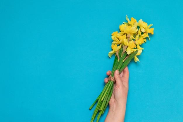 Weibliche hand mit einem blumenstrauß der gelben narzissen