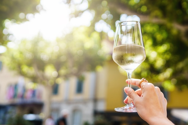Weibliche hand mit einem glas weißwein
