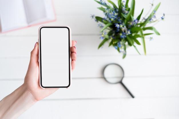 Weibliche hand mit einem smartphone. weißer leerer bildschirm. tabelle mit notizbuch und blumen ein