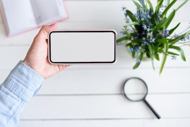 Weibliche hand mit einem smartphone. weißer leerer bildschirm. tisch mit notebook und blumen