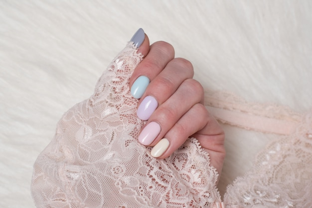 Weibliche hand mit einer mehrfarbigen leichten maniküre. spitze in der hand. nahansicht