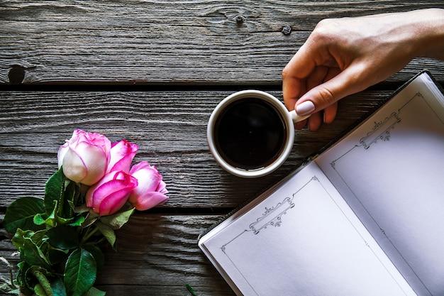 Weibliche hand mit einer tasse kaffee, buch und blumen auf holzoberfläche