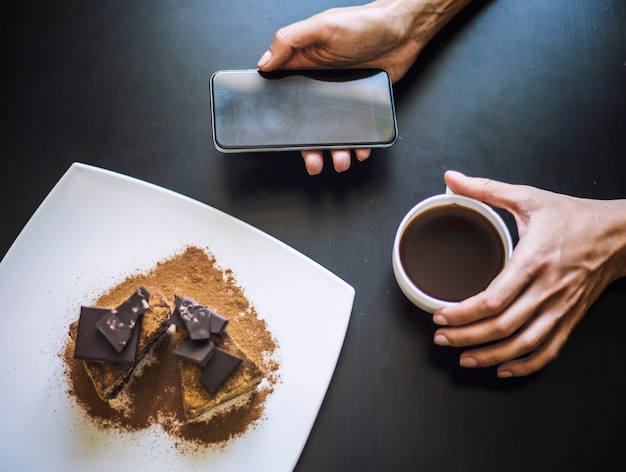 Weibliche hand mit einer tasse kaffee, einem telefon und einer schönen schokoladenkuchen-nahaufnahme auf dem tisch