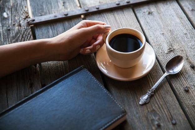 Weibliche hand mit einer tasse kaffee, notizen machend. es funktioniert aufzeichnungen. geschäft