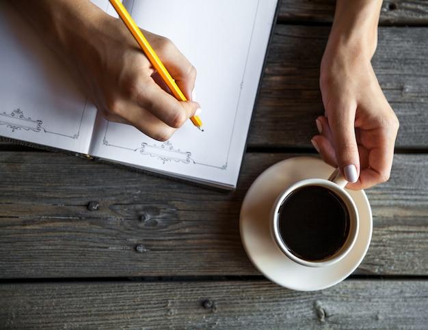 Weibliche hand mit einer tasse kaffee, notizen machend. es funktioniert aufzeichnungen. unternehmen