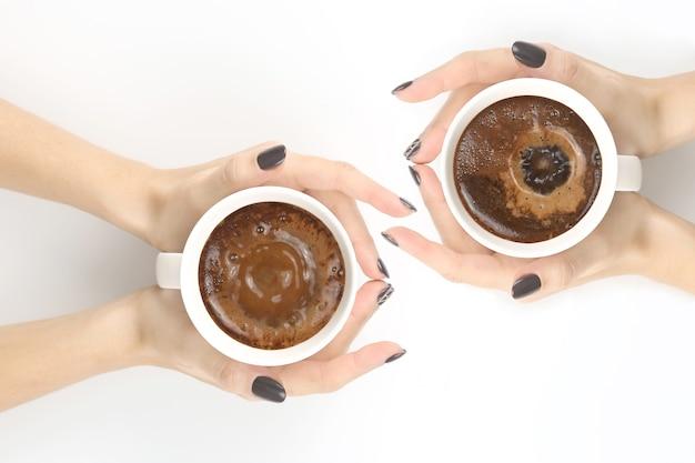 Weibliche hand mit einer tasse schwarzen kaffees auf weißer tischplatte