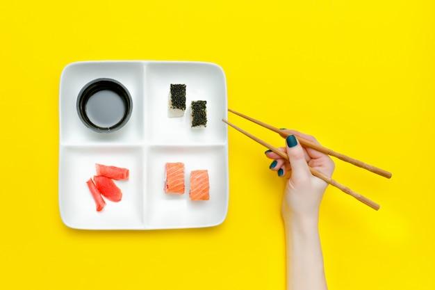 Weibliche hand mit essstäbchen und platte mit sushi