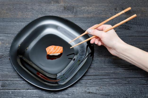 Weibliche hand mit essstäbchen und sushi. schwarzer hölzerner hintergrund. ansicht von oben
