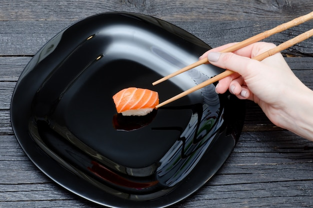 Weibliche hand mit essstäbchen und sushi