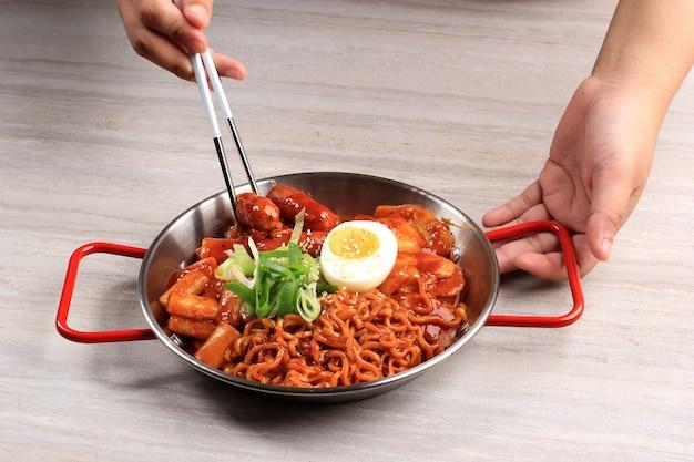 Weibliche hand mit essstäbchen zum essen von rabokki (ramen oder koreanische instant-nudeln und tteokbokki) in würziger koreanischer sauce, mit halb gekochtem ei und geschnittener grüner zwiebel
