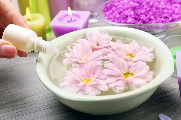 Weibliche hand mit flasche essenz und schüssel aroma spa wasser auf holztisch