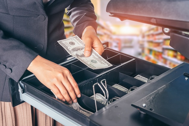 Weibliche hand mit geld im supermarkt-shop.