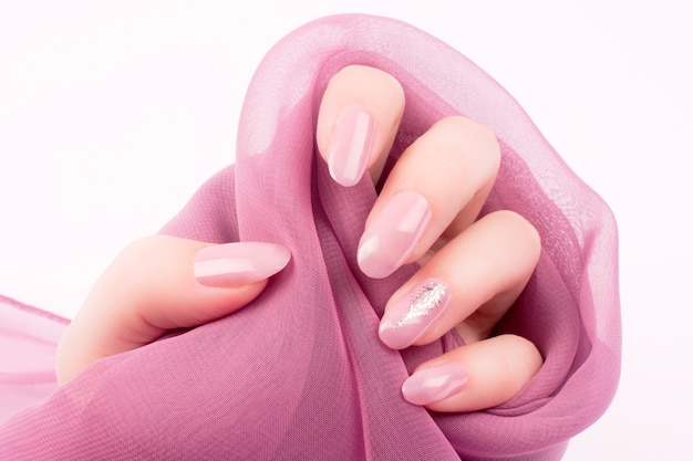 Weibliche hand mit glänzendem rosa rosennägeln-manikürekonzept