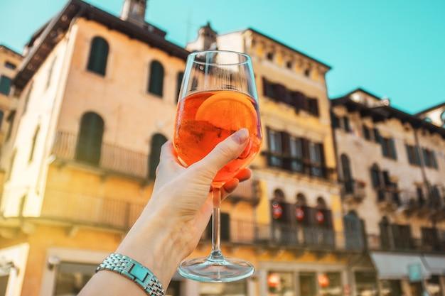 Weibliche hand mit glas des orange alkoholischen cocktail-spritzes auf dem hintergrund der alten gebäude, sonniger urlaubssommertag in verona, italien.