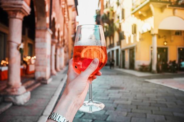 Weibliche hand mit glas des orange alkoholischen cocktail-spritzes auf dem hintergrund der straße, alte gebäude, sonniger urlaubssommertag in verona, italien.
