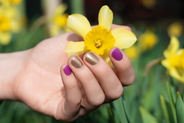 Weibliche hand mit gold- und purpurnageldesign, das blütenblüte hält