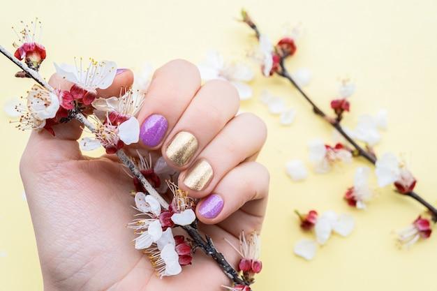 Weibliche hand mit gold- und purpurnageldesign, der blütenkirschzweig hält.
