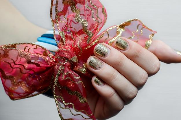 Weibliche hand mit goldnageldesign und rotem bogen.