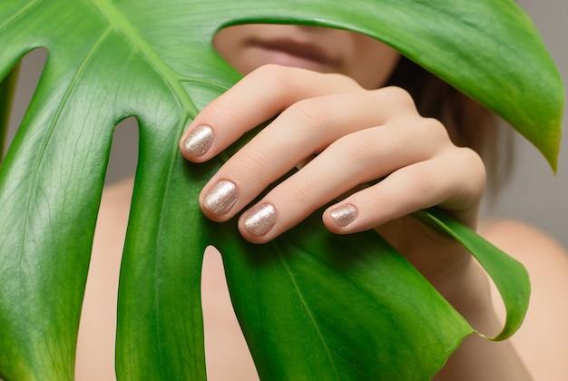 Weibliche hand mit goldnageldesign.