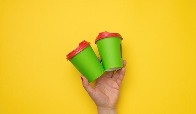 Weibliche hand mit grünem einwegpapierbecher auf gelbem hintergrund
