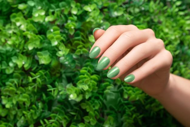 Weibliche hand mit grünem nageldesign. nagellack-maniküre in glitzergrün. frauenhand auf grün verlässt naturhintergrund