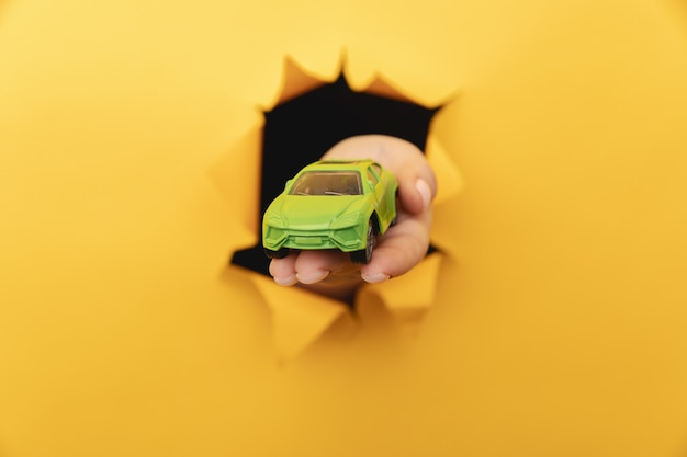 Weibliche hand mit hausauto durch einen riss in gelber papierwandnahaufnahme