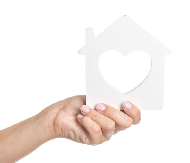 Weibliche hand mit hausfigur. hypothekenkonzept