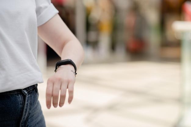 Weibliche hand mit intelligentem armband. intelligente uhr auf dem handgelenk.