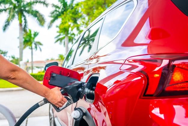 Weibliche hand mit kraftstoffpistole und rotem auto