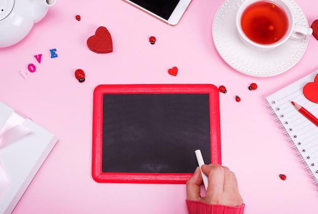 Weibliche hand mit kreide auf leerer schwarzer tafel