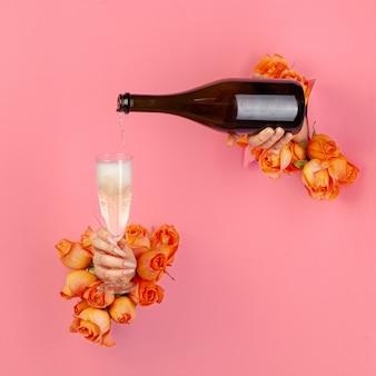 Weibliche hand mit maniküre, die champagner in ein glas durch ein loch in einem zerrissenen papier gießt, das mit rosen verziert wird