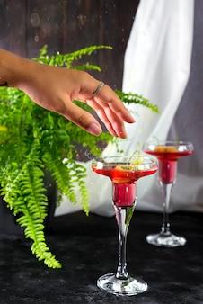 Weibliche hand mit margarita-cocktail, garniert mit makronen und beeren auf einem dunklen hintergrund