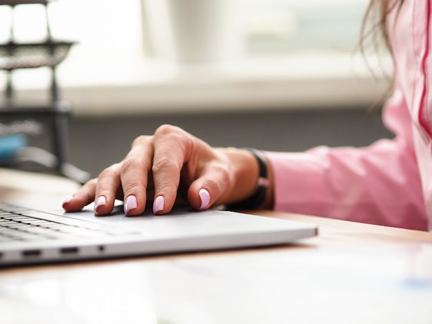 Weibliche hand mit mode-maniküre liegt nahe laptop