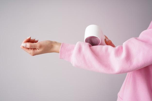 Weibliche hand mit modernem stoffrasierer und -pullover auf einem farbhintergrund.