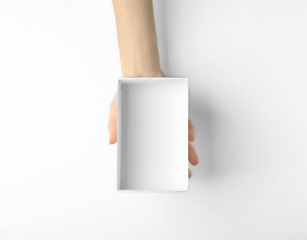 Weibliche hand mit offenem kasten auf weißem hintergrund