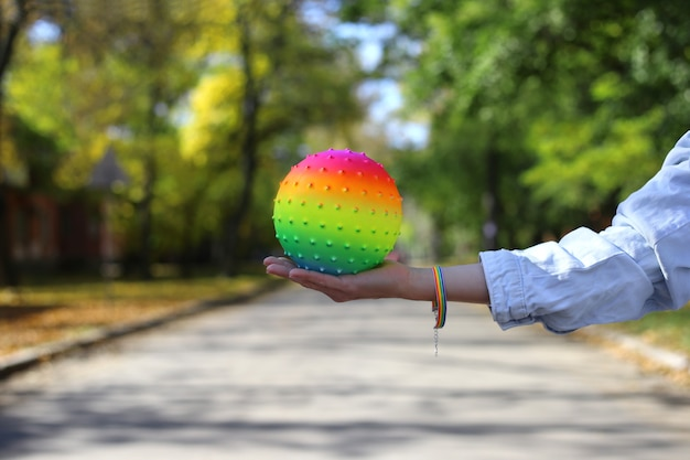 Weibliche hand mit regenbogenarmband hält regenbogenball auf dem parkhintergrund. lgbt-konzept