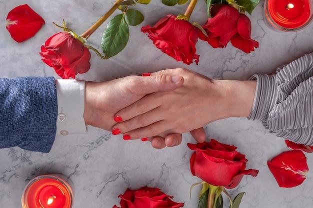 Weibliche hand mit rotem nagellack liegt im männlichen valentinstag 14 verlobung romantischer abend