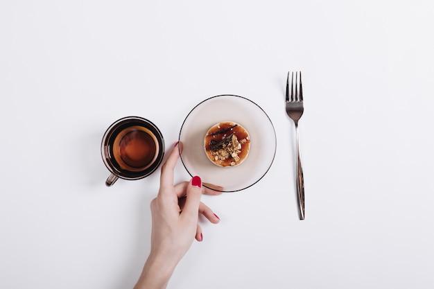 Weibliche hand mit rotem nagellack setzte auf dem tisch kuchen auf eine untertasse, einen tee und eine gabel