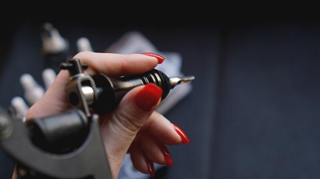 Weibliche hand mit roten nägeln, die tätowiermaschine halten. hand ohne handschuhe - übungs- und trainingstattoo. dunkler hintergrund