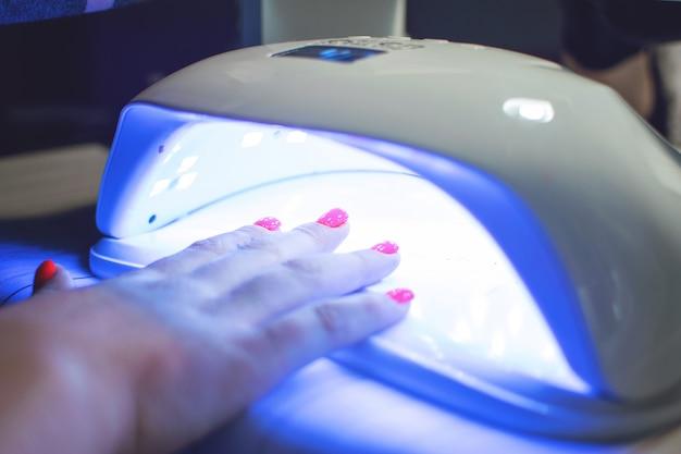 Weibliche hand mit roten nägeln in led-lampe
