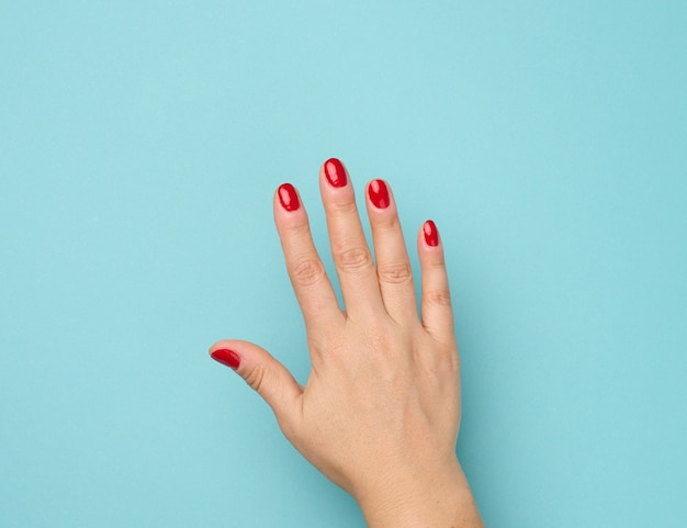Weibliche hand mit roter maniküre auf blauem hintergrund erhoben