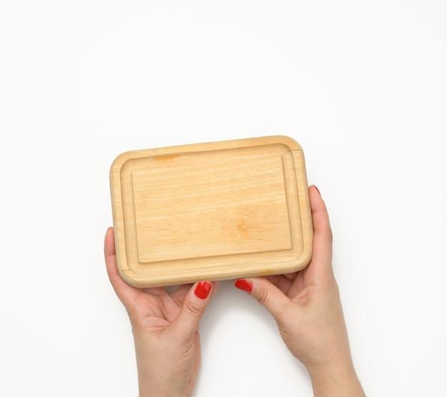 Weibliche hand mit roter maniküre hält leeres hölzernes rechteckiges küchenschneidebrett auf weißem hintergrund, draufsicht
