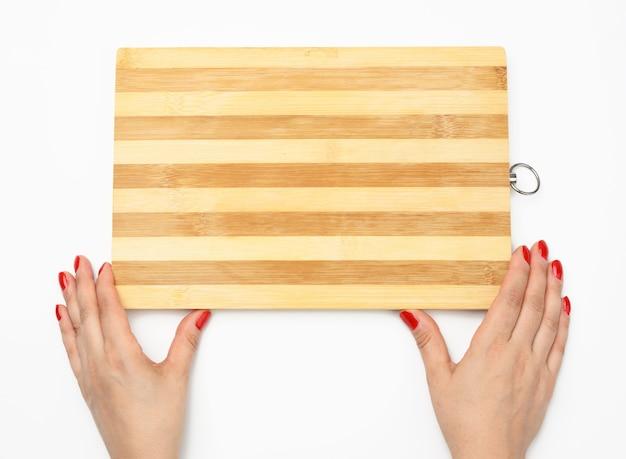 Weibliche hand mit roter maniküre hält leeres rechteckiges küchenschneidebrett aus holz auf weißem hintergrund