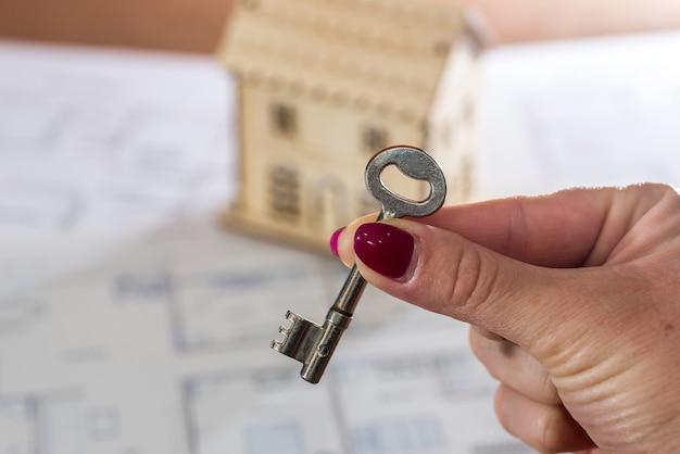 Weibliche hand mit schlüssel und spielzeughaus auf plan