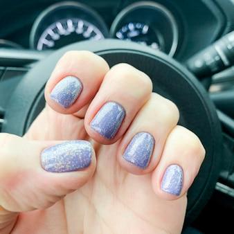 Weibliche hand mit schöner maniküre im auto