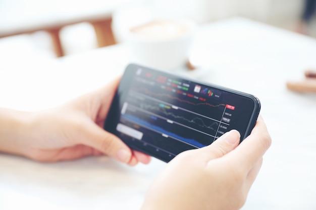 Weibliche hand mit smartphone, das online in der kaffeestube mit aktien handelt