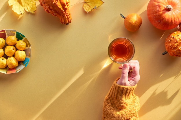 Weibliche hand mit tasse tee, orange kürbissen und pappteller mit quitte, kopierraum
