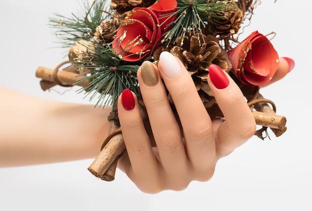 Weibliche hand mit weihnachtsnageldesign.