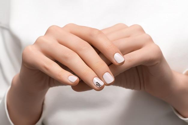 Weibliche hand mit weißem nageldesign, nahaufnahme.