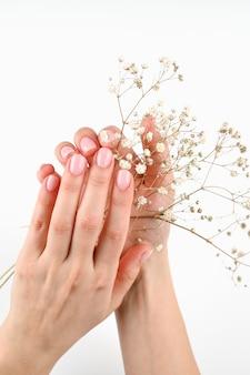 Weibliche hand mit weißen blumen auf weiß